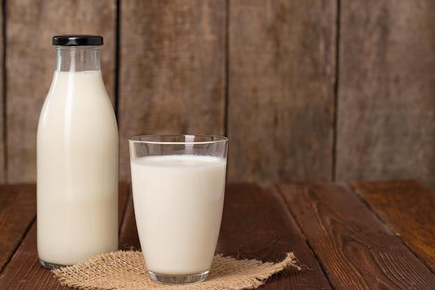 병 및 나무 테이블에 우유의 유리