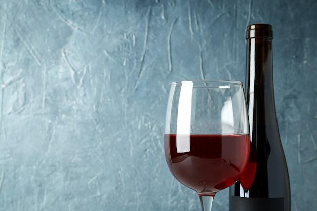 青いテクスチャ背景に赤ワインのボトルとグラス