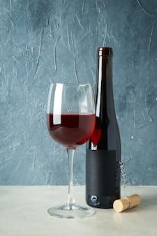 赤ワインのボトルとグラス、そして青い織り目加工の背景にコルク栓抜き