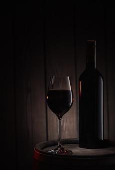 ボトルと赤ワインのガラスは古い木製の樽の上に立つ