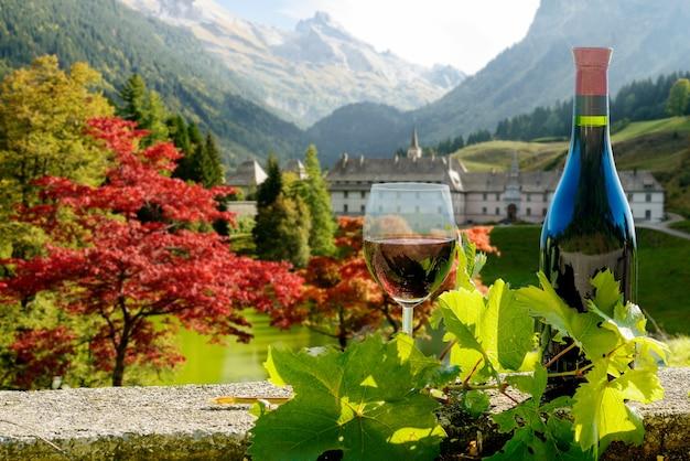 Бутылка и бокал красного вина с осенним горным пейзажем во французских альпах