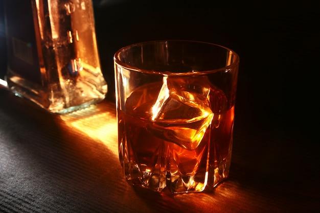 Бутылка и стакан виски или бурбон со льдом на черном каменном столе.