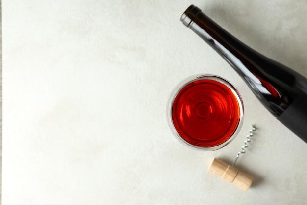 ワインのボトルとグラス、そして白い織り目加工のテーブルのコルク栓抜き