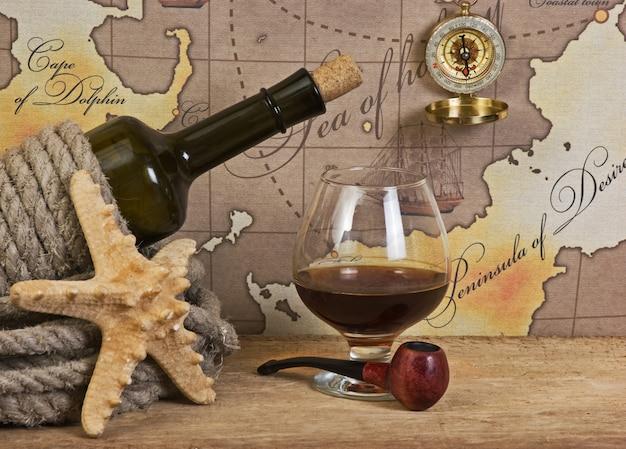 병 및 오래 된지도의 배경에 와인 한 잔