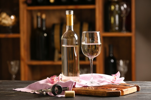 Бутылка и бокал вина на столе