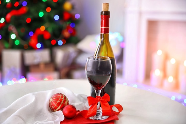 カラフルなボケ味のライトの表面に対してクリスマスの装飾が施されたワインのボトルとグラス