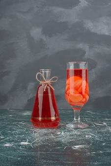 Бутылка и стакан с соком на мраморном столе.