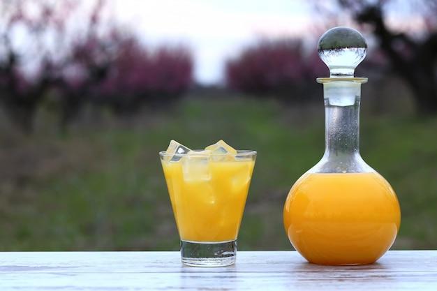 ボトルとグラスにオレンジジュース、花桃の木の庭でガラスのアイスキューブ