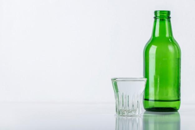 흰색 테이블에 소주 병 및 유리. 한국 전통 술