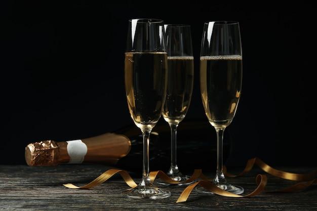 Бутылка и бокалы шампанского и фигурные ленты на деревянном столе