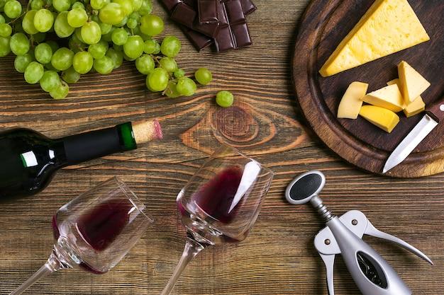 木製の背景にワイン、チーズ、熟したブドウのボトルとグラス。上面図。スペースをコピーします。フラットレイ。静物