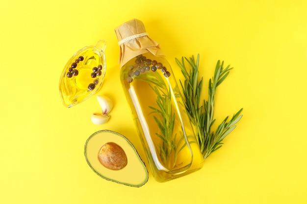 Бутылка и соусник из масла и ингредиентов на желтом фоне