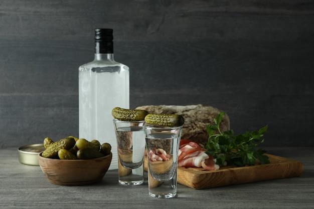 Бутылка и рюмки с напитками и разные закуски на сером столе