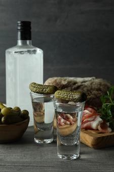 Бутылка и рюмки водки и разные закуски на сером столе