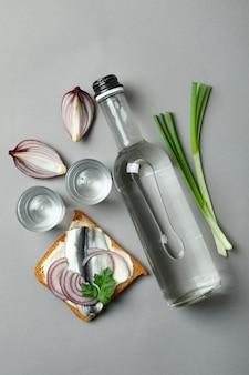 Бутылка и рюмки водки и закуски на сером фоне