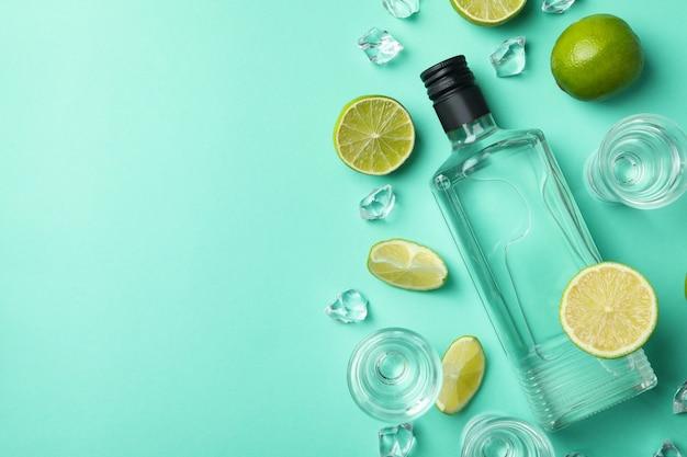 Бутылка и рюмки водки, лайма и льда на мятой, вид сверху