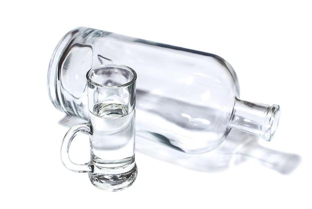 Бутылка и небольшой стакан, наполненный прозрачным крепким напитком