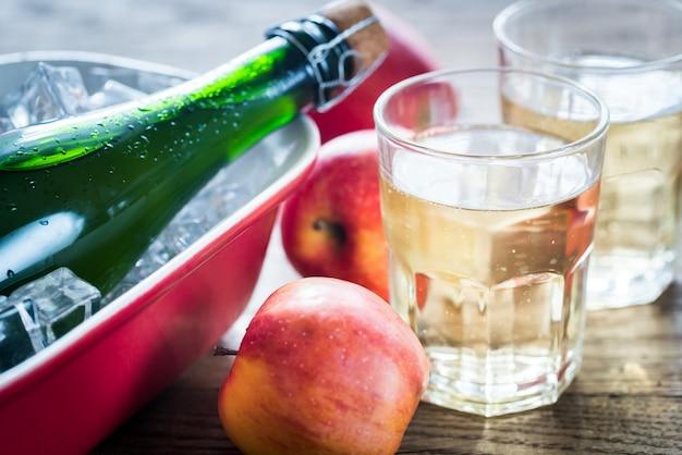 Бутылка и два стакана сидра на деревянном столе