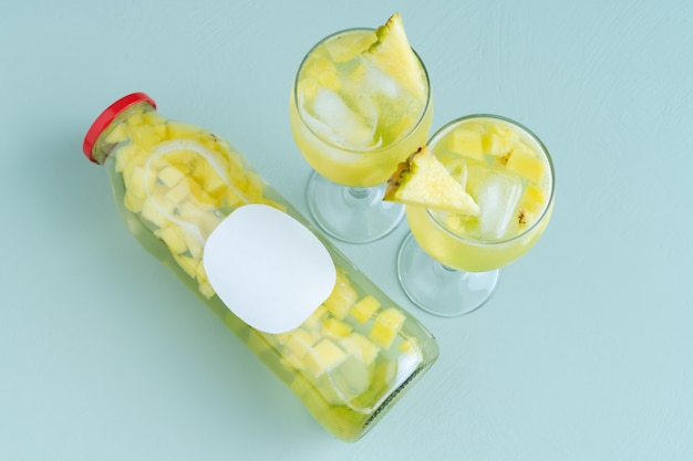 Бутылка и два стакана с водой и кусочками фруктов на синем фоне. скопируйте пространство.