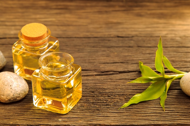 Bottle of aroma essential oil or spa and natural green leave on wooden table Premium Photo