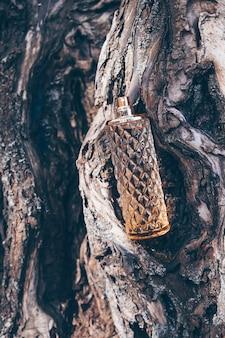 Bottle of aromatic woody luxury perfume on tree bark woody fragrance aroma template