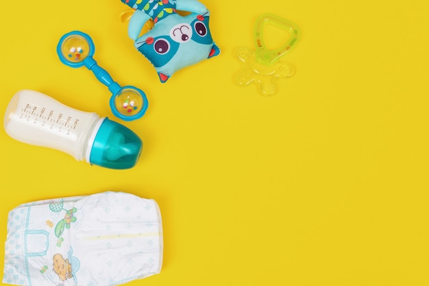 Bottle of baby milk formula with teething, diapers and toys on yellow background