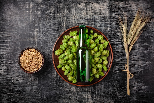 A bottle of beer on a green hop in a plate with grain and spikelets of wheat against the background