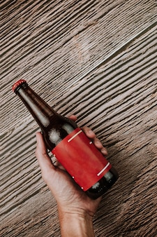 A bottle of beer held by a hand on a wooden background