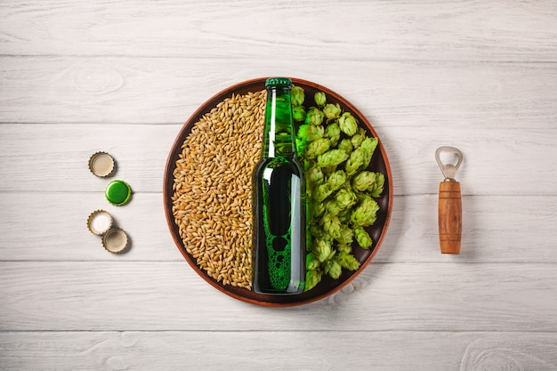 A bottle of beer on a plate with green hops and oat grain with opener and corcks on a white wooden board