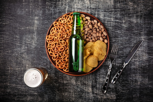 A bottle of beer on a plate with salted ookies pretzels, pistachio nuts and chips on a black scratched chalk board