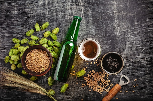 A bottle of beer with green hops, oat, wheat spikelets, opener and glasses with dark and light beer