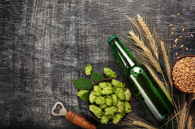 A bottle of beer with a green hops, spikelets, bowl oats and opener on a black scratched chalk board