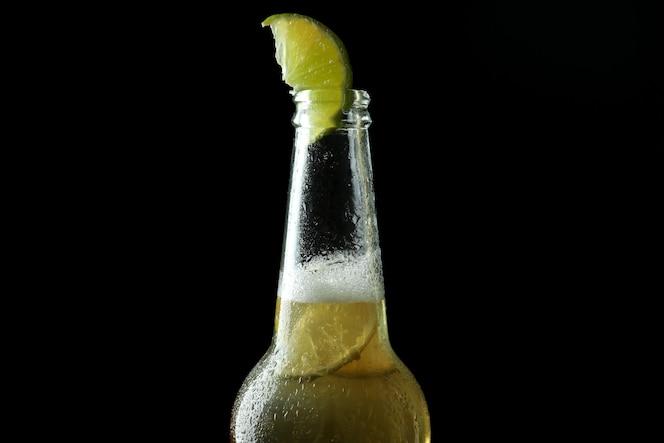 bottiglia di birra con calce sul nero