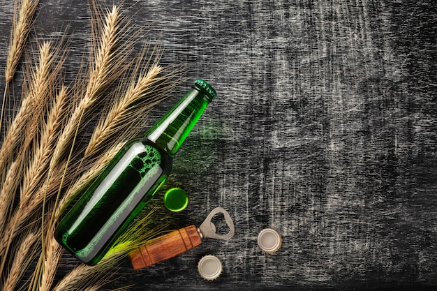 A bottle of beer with spikelets and opener on a black scratched chalk board