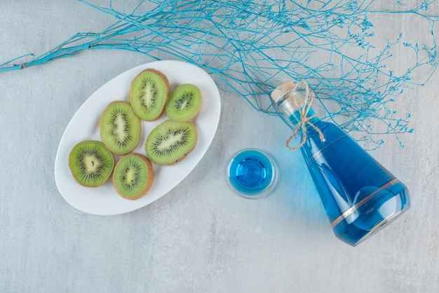 A bottle of blue juice with kiwi on white plate