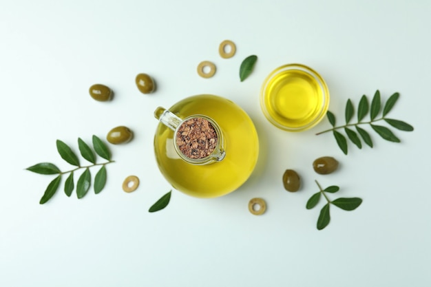 Bottle and bowl of oil, olives and twigs on white surface