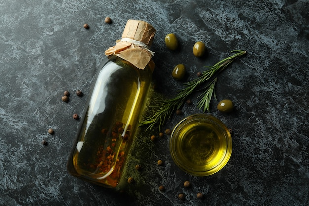 Bottle and bowl with olive oil and spices on black smokey