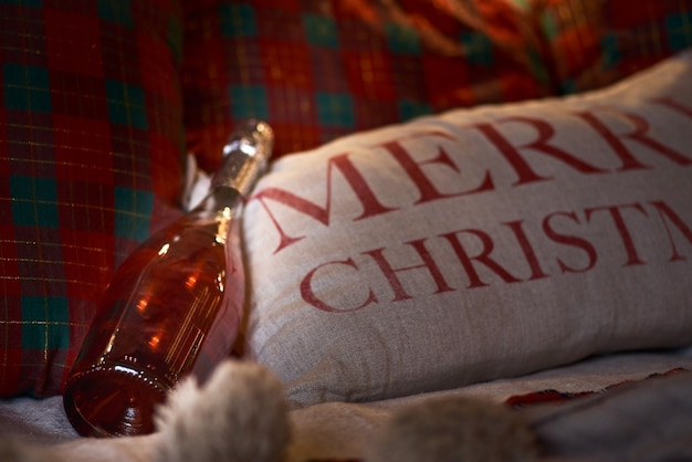 Bottle of champagne in bed. christmas party. pillow with the inscription merry christmas.