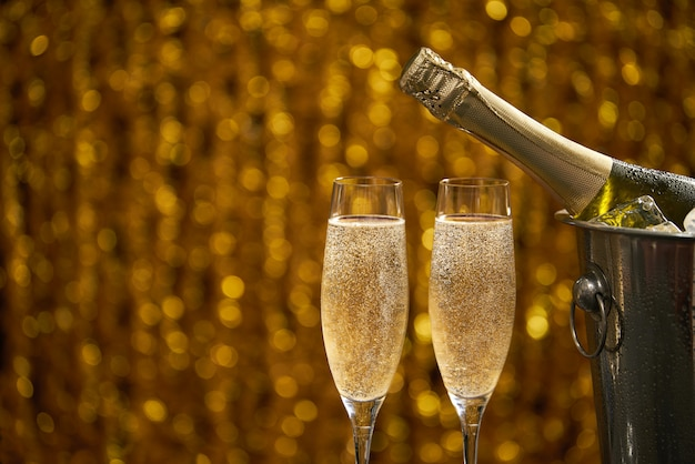 Bottle of champagne in a bucket with ice  and two glasses of champagne on golden bokeh background