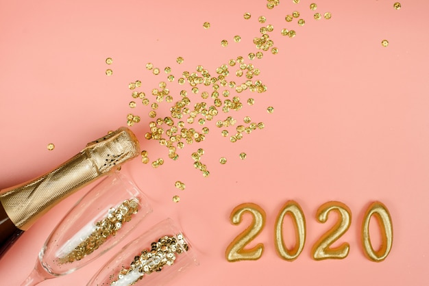 Bottle of champagne, clear glasses with gold confetti and gold numbers on a pink pastel