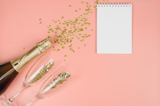 Bottle of champagne and clear glasses with gold confetti