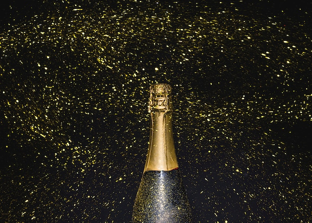 Bottle of champagne in flying golden glitters