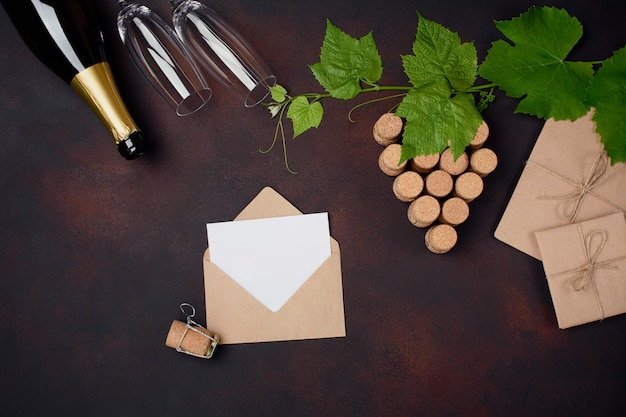 Bottle of champagne, gape bunch of cork with leaves, two wineglass, envelope and letter on rusty background.