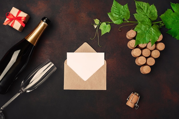 Bottle of champagne, gape bunch of cork with leaves, two wineglass, gift box, envelope and letter on rusty background.