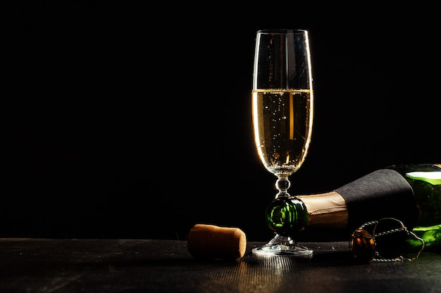 Bottle of champagne and glasses over dark