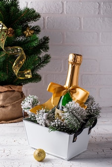 Bottle of champagne in a gold wrapper with christmas decoration