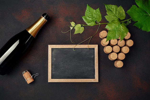 Bottle of champagne, grape bunch of cork with leaves and chalkboard on rusty background