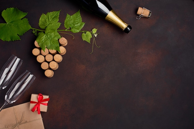 Bottle of champagne, grape bunch of cork with leaves, wineglass gift box on rusty background