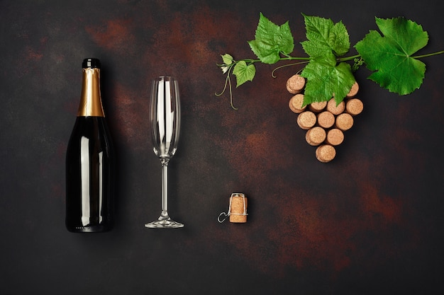 Bottle of champagne, grape bunch of cork with leaves and wineglass on rusty background