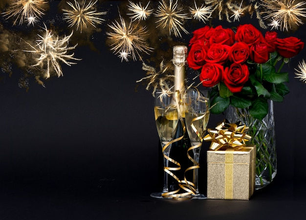 Bottle of champagne, red roses, golden gift with beautiful golden fireworks on black background